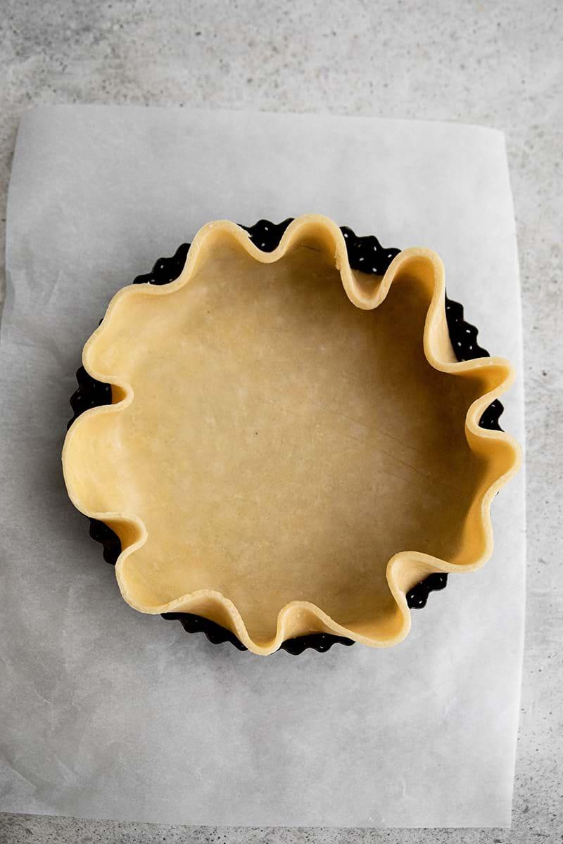 Plano aéreo de la masa para tarta colocada groseramente en el molde.
