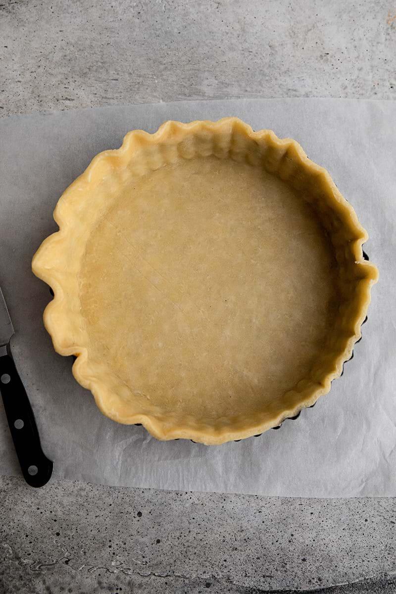 Plano aéreo de del molde de tarta forrado con la masa.