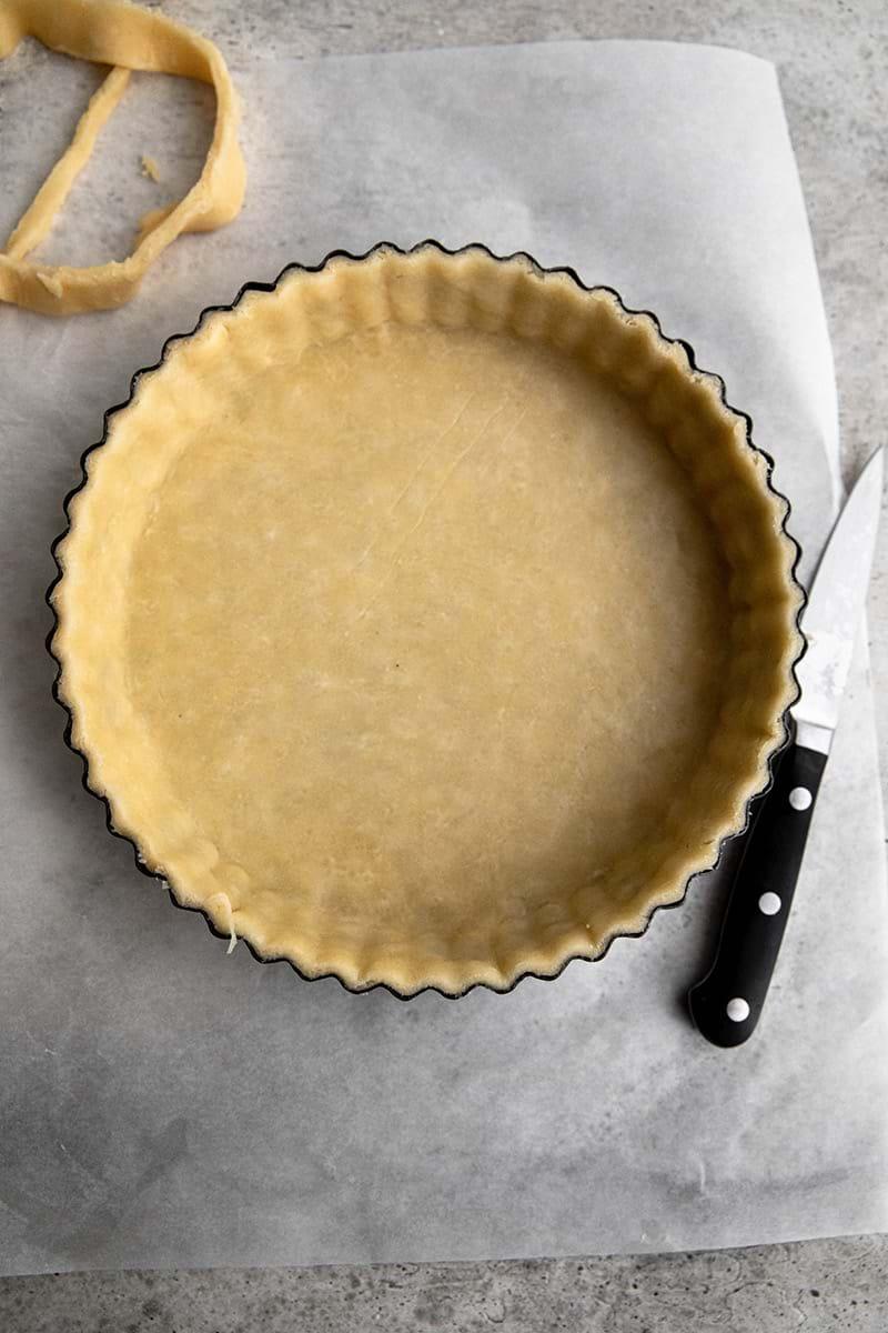 Plano aéreo de del molde de tarta forrado con la masa con los bordes cortados a cuchillo.