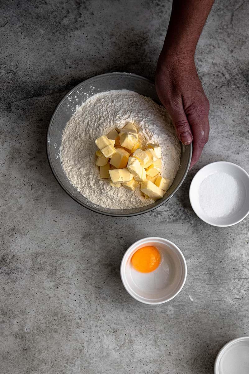 Plano aéreo de un bol con los ingredientes secos y la manteca cortada en cubos con una mano lista para trabajar la masa.