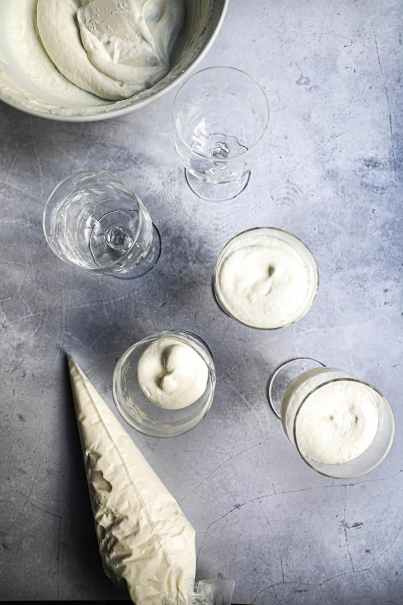 4 copas de vino rellenas con mousse de chocolate blanco y una manga a su lado con el bol de mousse de chocolate blanco en el extremo superior del cuadro.