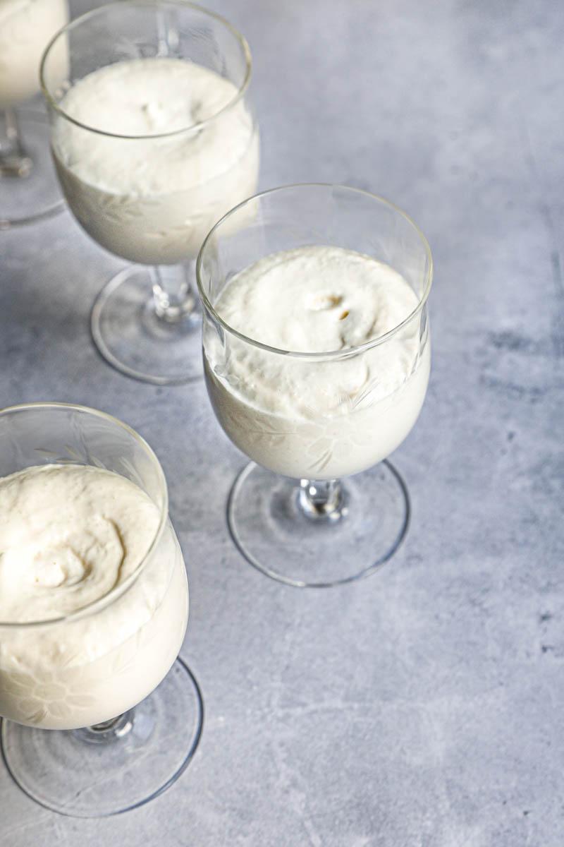 4 copas de vino rellenas con mousse de chocolate blanco vistas desde el costado.