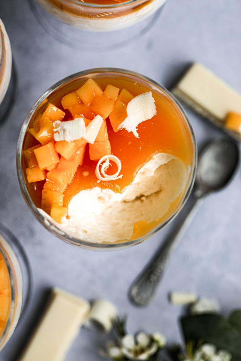 Primer plano de una copa de vino rellanas de mousse de chocolate blanco cubiertas con jalea de mango y mango cortado vistas desde arriba, con una mousse que le falta un bocado.