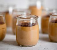 Plano de 90° de una vasito relleno de mousse de dulce de leche con varios vasitos detrás que están borrosos