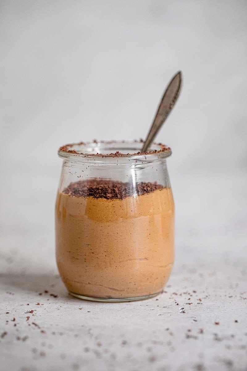 Plano de 90° de un vasito de vidrio relleno de mousse de dulce de leche cubierta de chocolate rallado