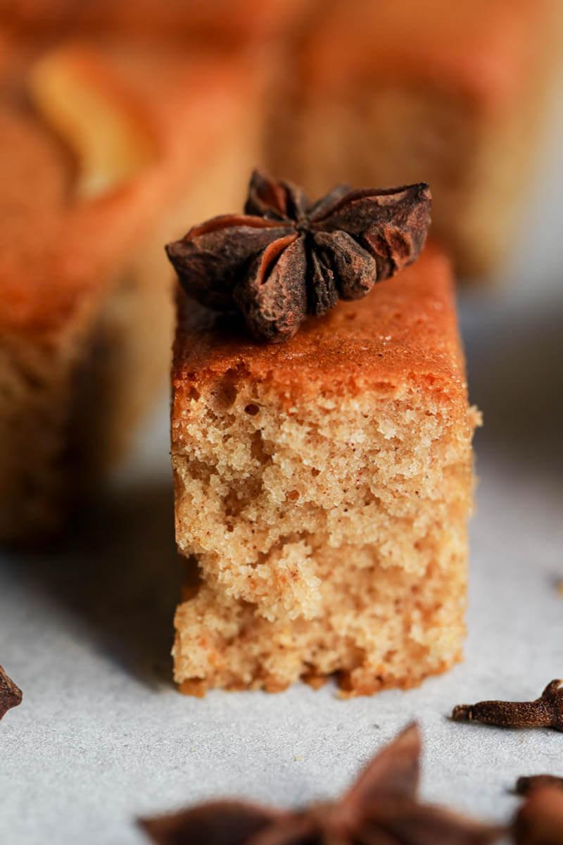 Un mini pan de miel y especias cortado con el fondo borroso y un bastón canela en el ángulo inferior derecho