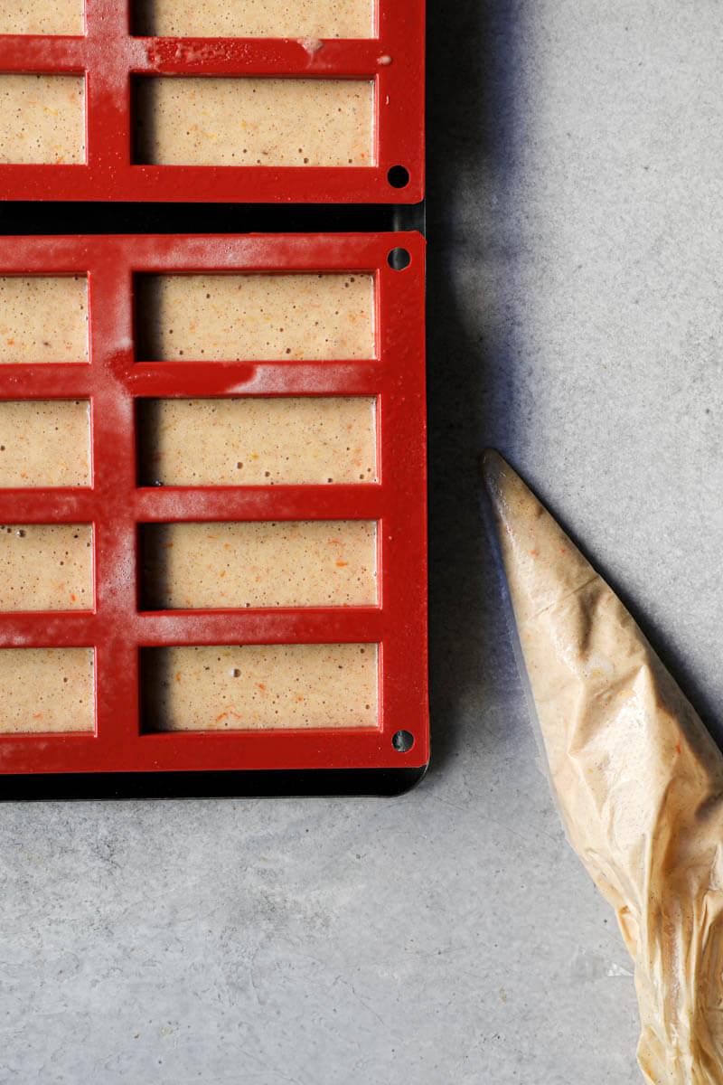 Los mini moldes de bizcocho rellenos con la mezcla del pan de especias y una manga a su lado