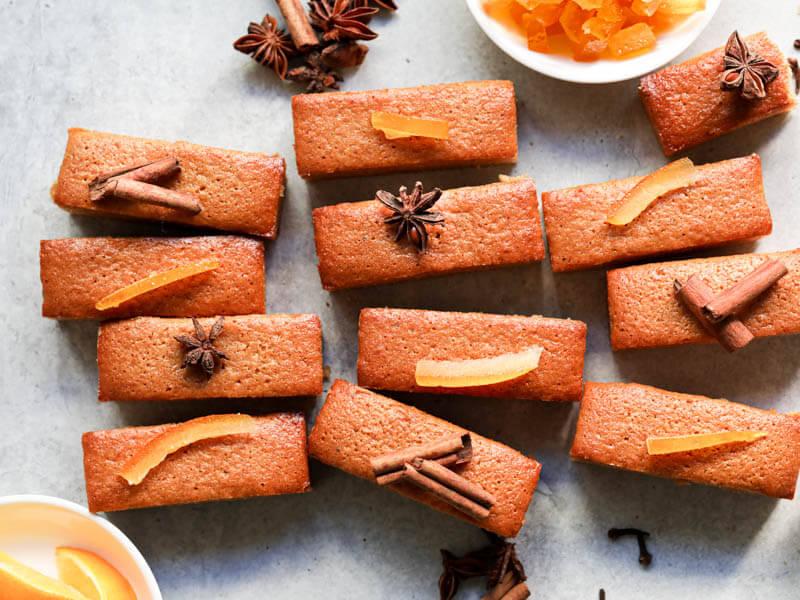Pain d'épices decorado con naranjas confitadas y anís formando un diseño irregular