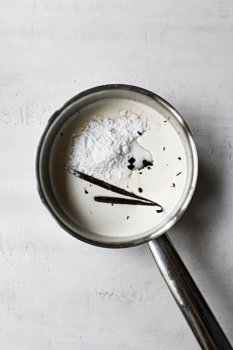 Una cacerola plateada pequeña rellena con crema de leche, vaina de vainilla y azúcar.