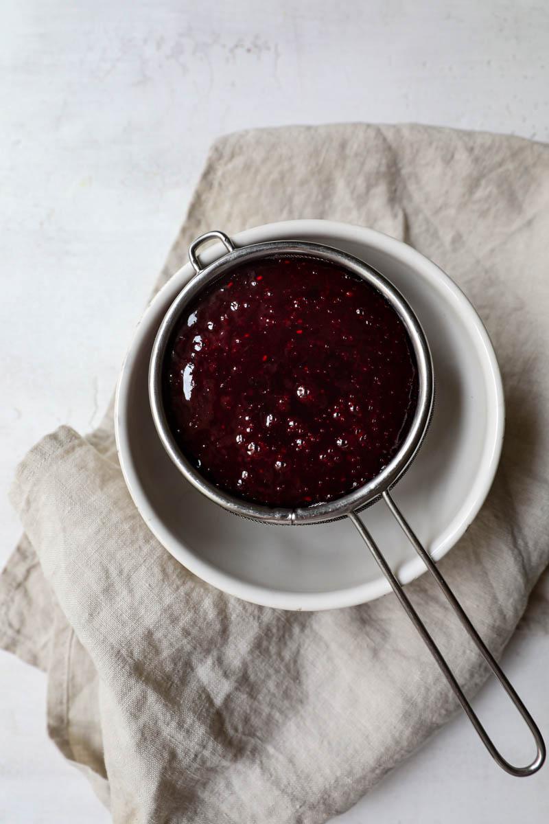 La salsa de frutos rojos procesada sobre un colador pequeño arriba de un bol blanco.