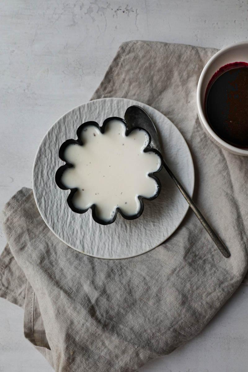 La panacota enfriada, dentro del molde sobre un plato blanco colocado sobre un trozo del género de lino beige.