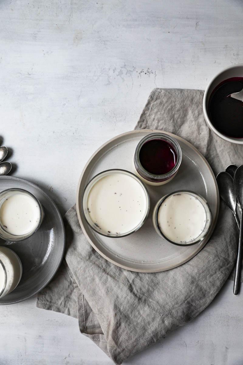 Los vasitos, dispuestos sobre dos platos medianos, rellenos con la panacota, enfriados, y algunos ya cubiertos con la salsa de frutos rojos, vista desde arriba.