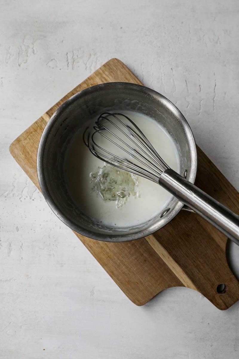 Gelatina y la leche caliente dentro de una cacerola pequeña con un batidor dentro.