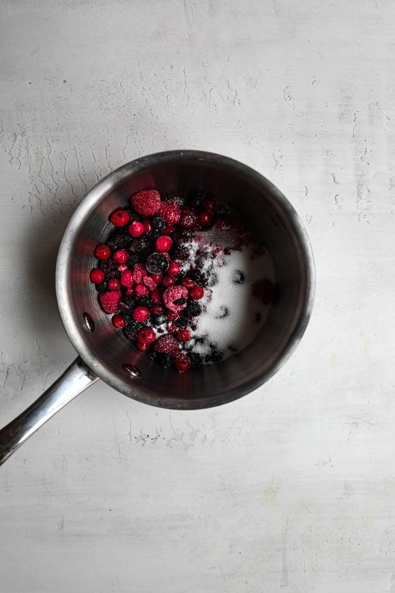 Frutos rojos y azúcar dentro de una cacerola pequeña.