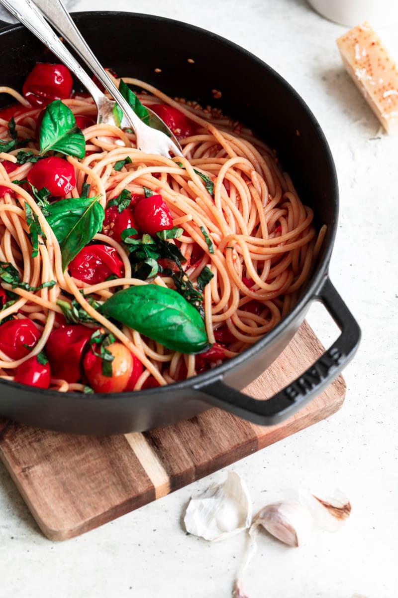 Primer plano de 45° de la mitad de una cacerola negra con pasta con salsa de tomate Cherry con una cuchara en el borde.