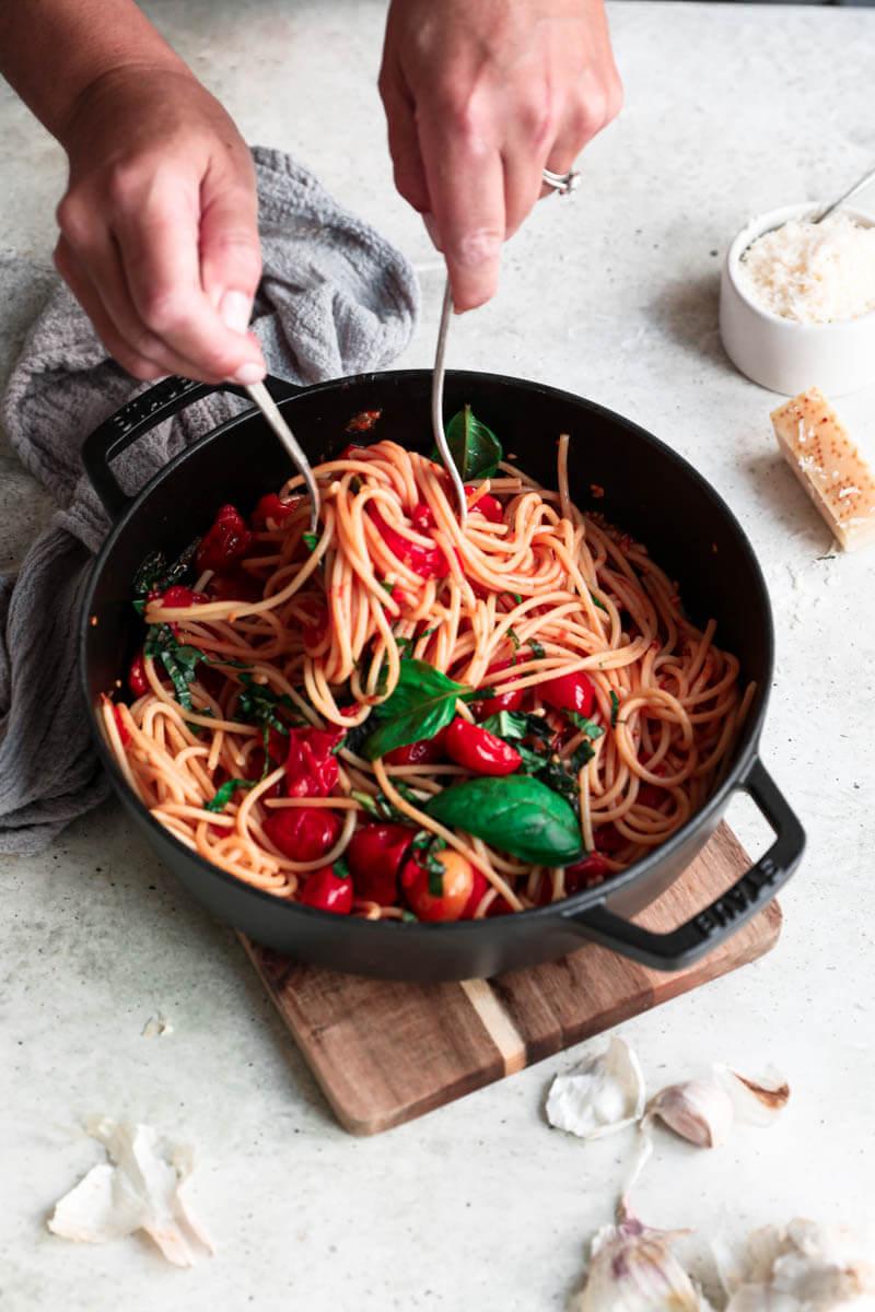Plano de 45° de 2 manos que sirven la pasta con salsa de tomates Cherry.
