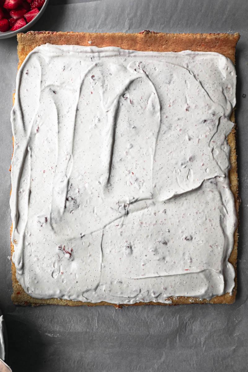 El pionono desenrollado sobre una hoja de papel vegetal cubierto con crema chantilly.