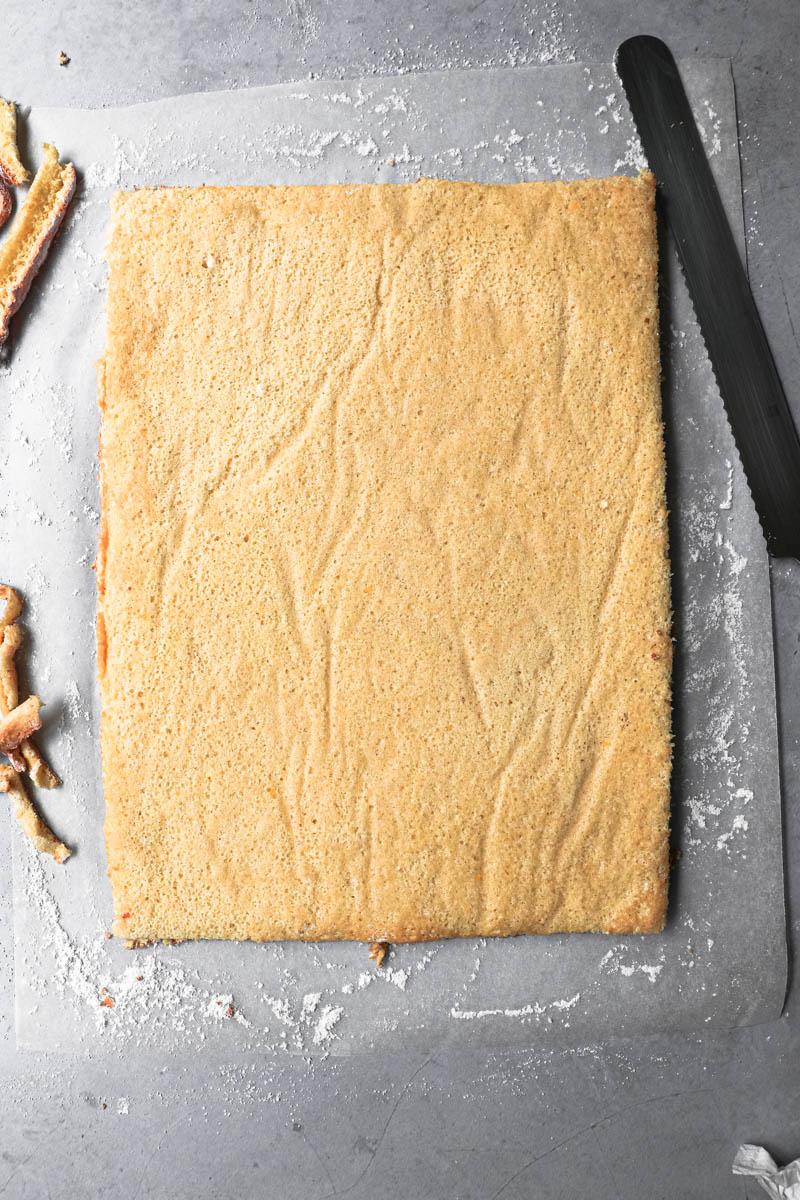 El pionono invertido sobre el papel vegetal cubierto con azúcar impalpable y los bordes cortados.