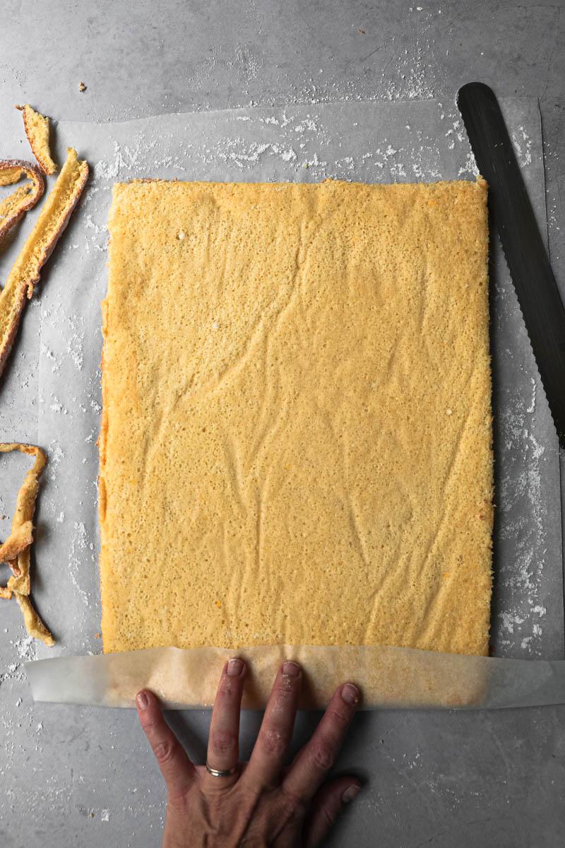 El pionono invertido sobre el papel vegetal cubierto con azúcar impalpable y los bordes cortados, y una mano doblando 3 cm de papel sobre el lado corto que cortado derecho.