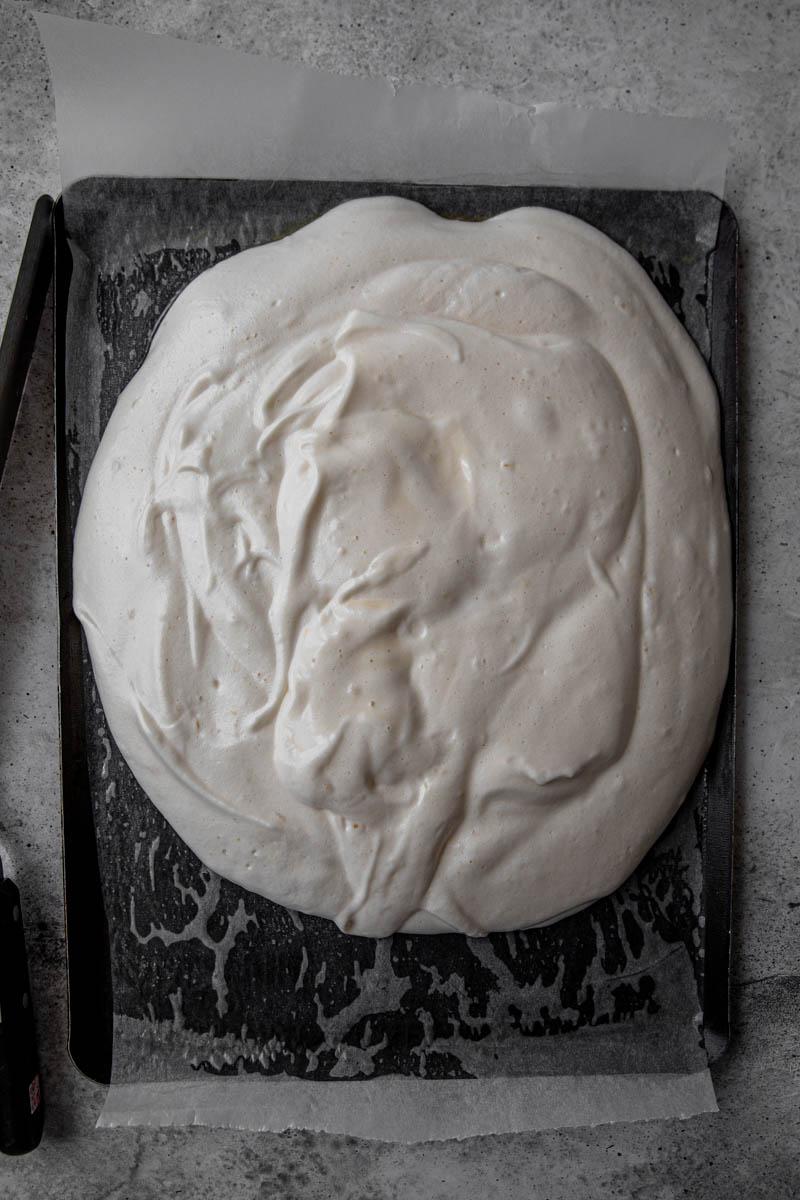 La masa del pionono sobre la placa para horno forrada con papel vegetal.