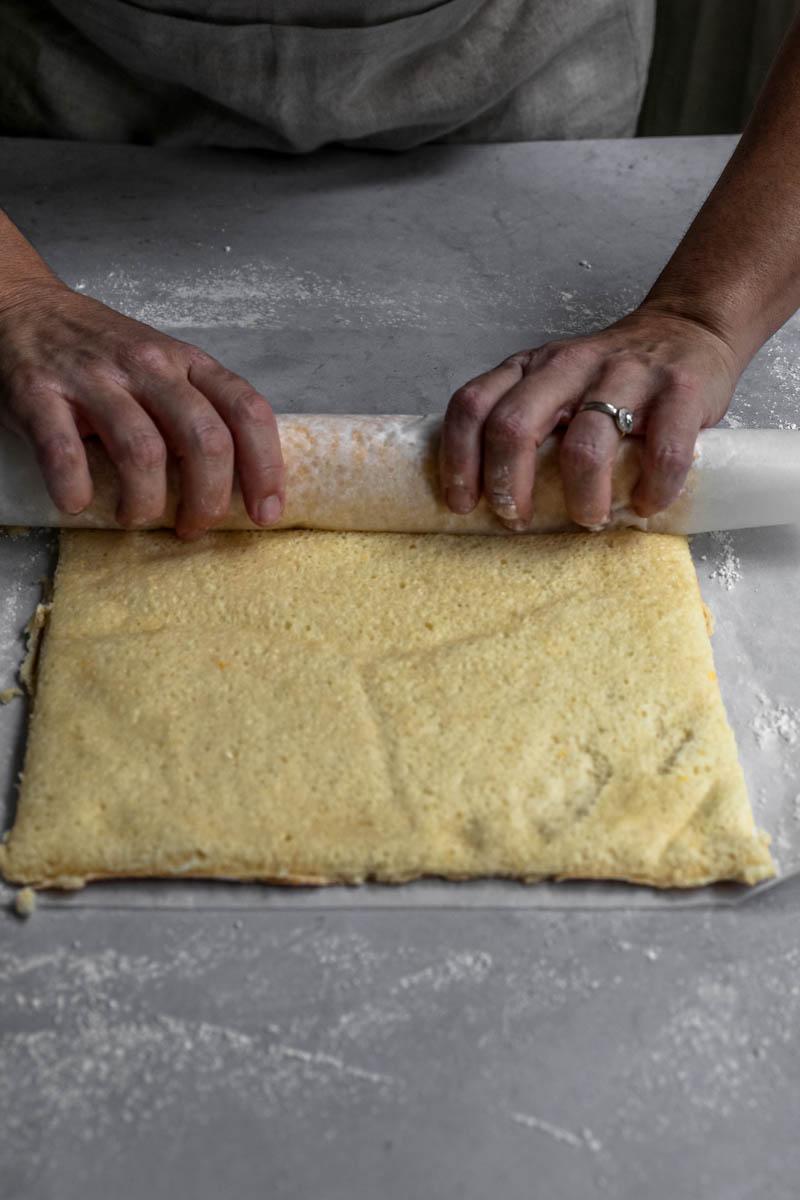 2 manos enrollando el pionono sobre una hoja de papel vegetal.