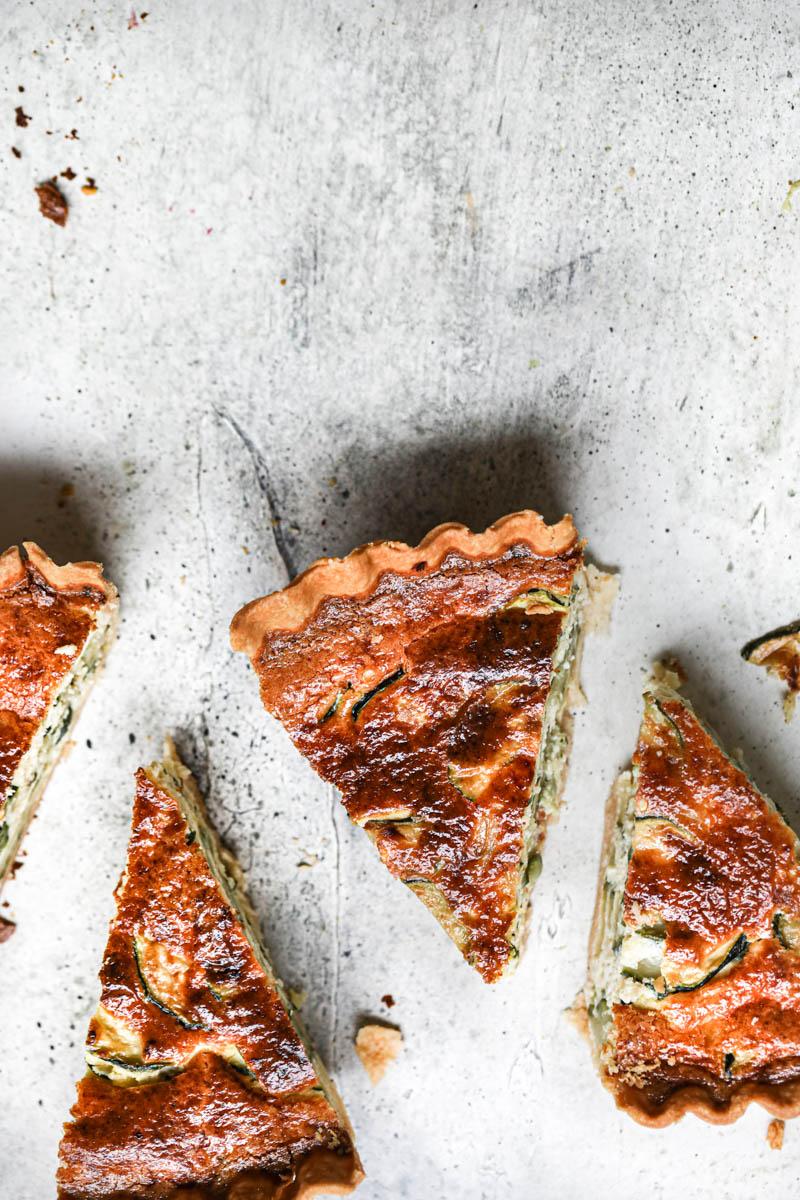 4 porciones de tarta de zapallitos vistas desde arriba colocadas en la parte de abajo del cuadro.