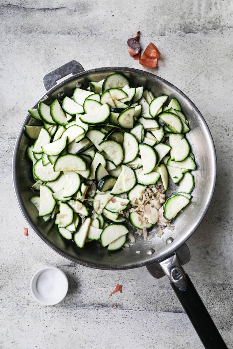 Los chalotes cortados y cocidos y los calabacines cortados crudos dentro de una sartén con un poco de aceite de oliva y los calaba
