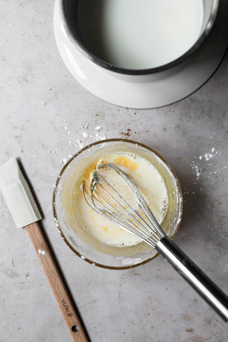 Un bol con la mezcla yemas/azúcar/maicena más 1/3 de la leche tibia con un batidor dentro.