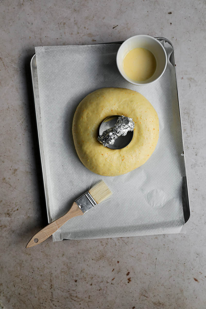 La rosca de Pascua con un agujero en el centro y un cortador pequeño dentro del agujero sobre una bandeja de horno forrada con papel vegetal con un pincel en sobre la bandeja y un bol con doradura en el otro extremo de esta.