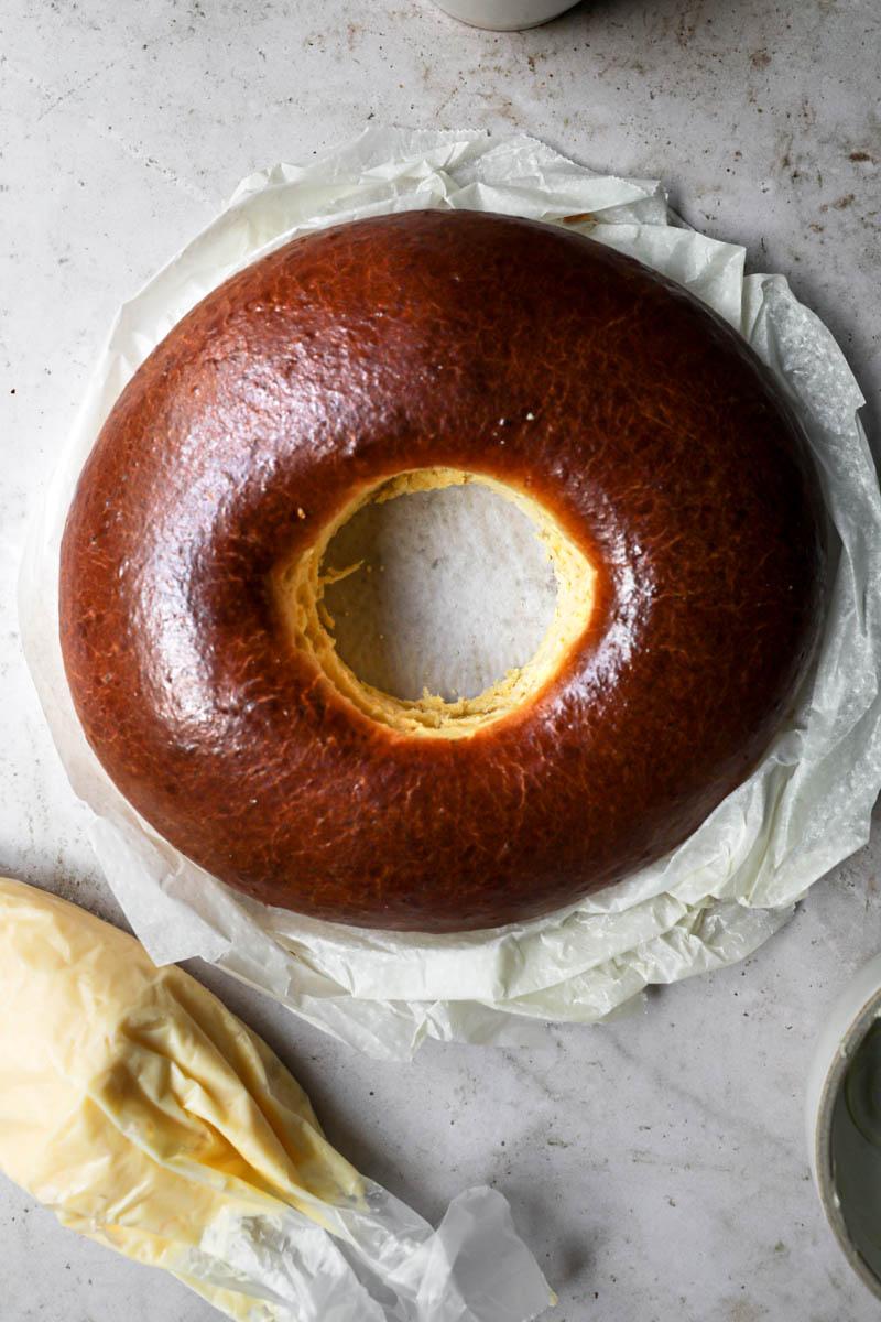 La rosca de Pascua horneada con una manga rellena de crema pastelera al costado.