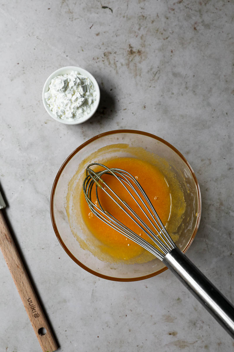 Las yemas y el azúcar mezcladas en un bol de vidrio y un pequeño bol con maicena a su lado.