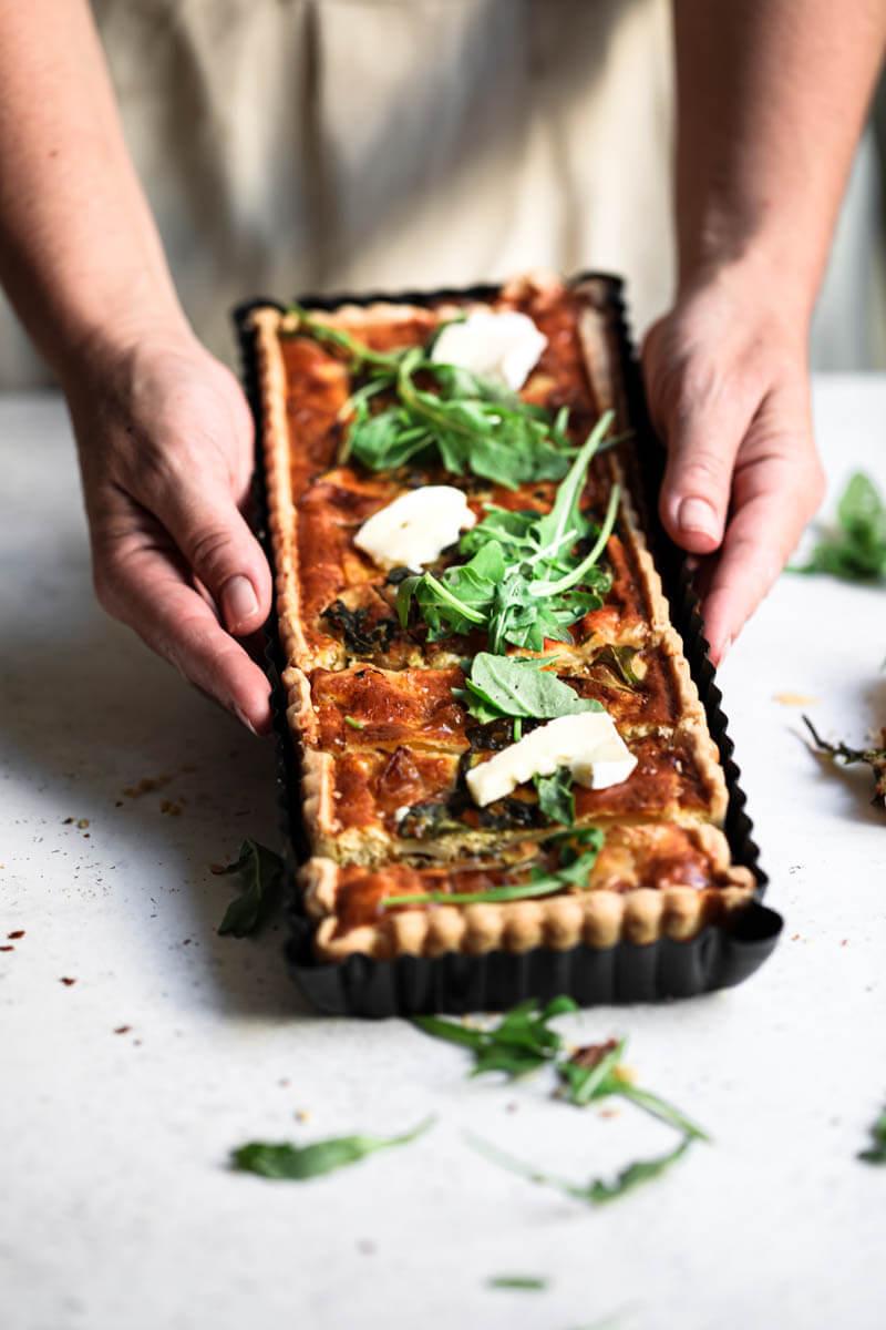 Plano de 45° de dos manos sosteniendo la tarta de cebolla en su molde