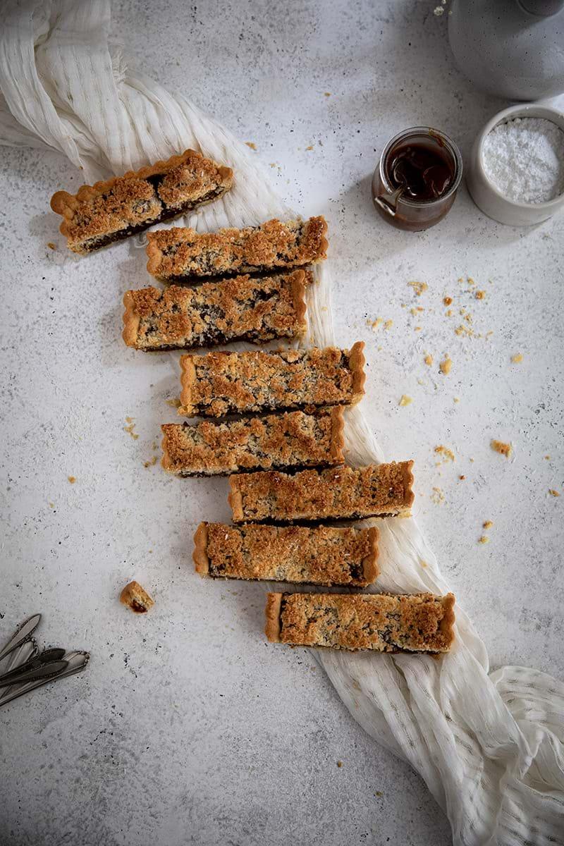 Plano aéreo de la tarta de coco rellena de dulce de leche cortada en porciones dispuestas en forma de zigzag