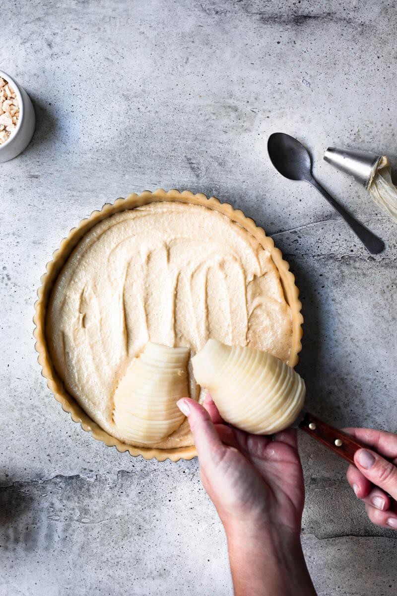 Plano aéreo de dos manos colocando la pera cortada sobre la base de la tarta