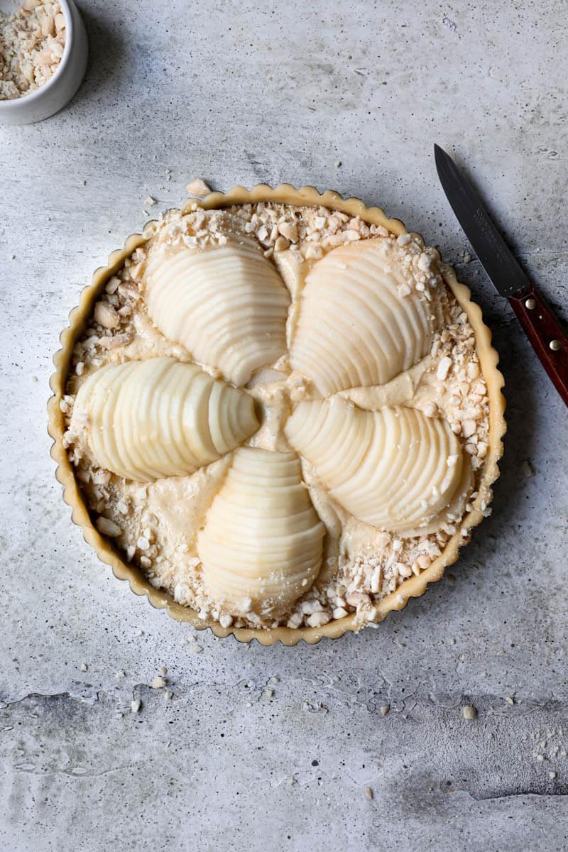 Plano aéreo de la tarta de peras con las almendras cortadas cubriendo el borde