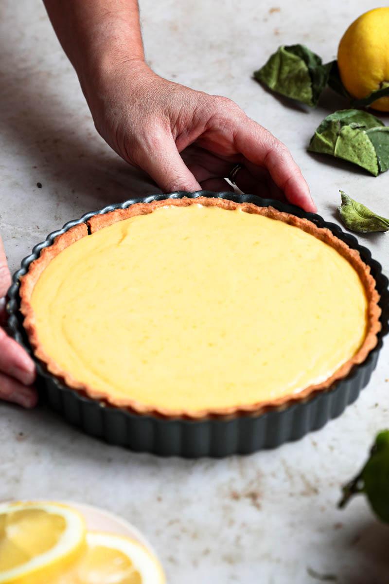Dos manos sosteniendo la tarta de limón sobre un plato de mármol antes de colocar en el refrigerador.