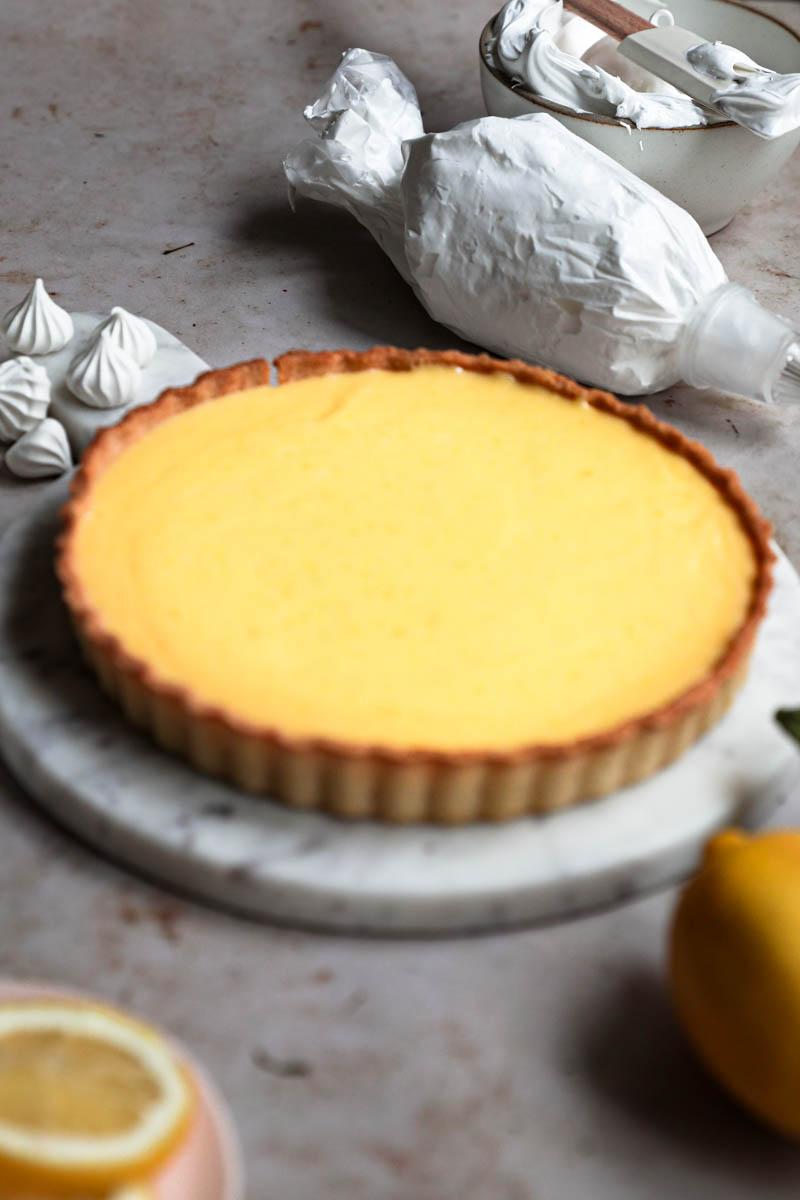 Primer plano de la tarta de limón con limones, merenguitos y una manga a alrededor.