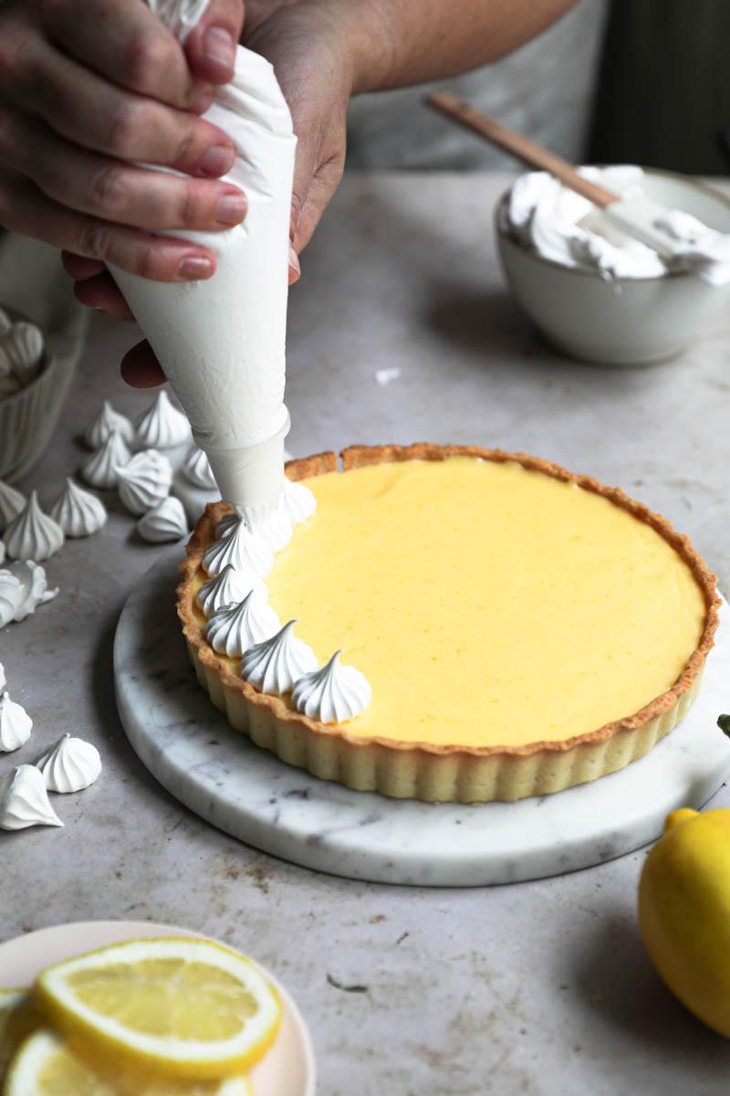 Dos manos decorando la tarta de limón con una manga rellena de merengue suizo.
