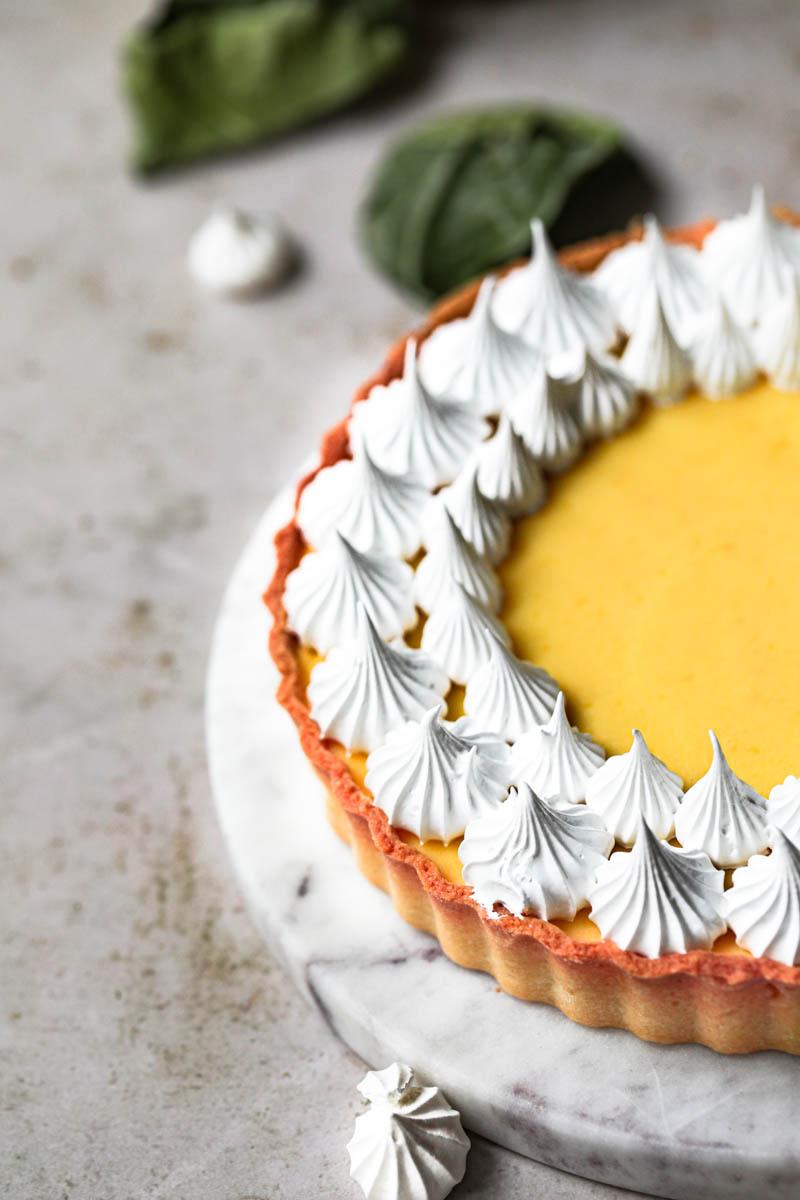 Primer plano de la mitad de la tarta de limón cubierta con merengue sobre un plato de mármol.