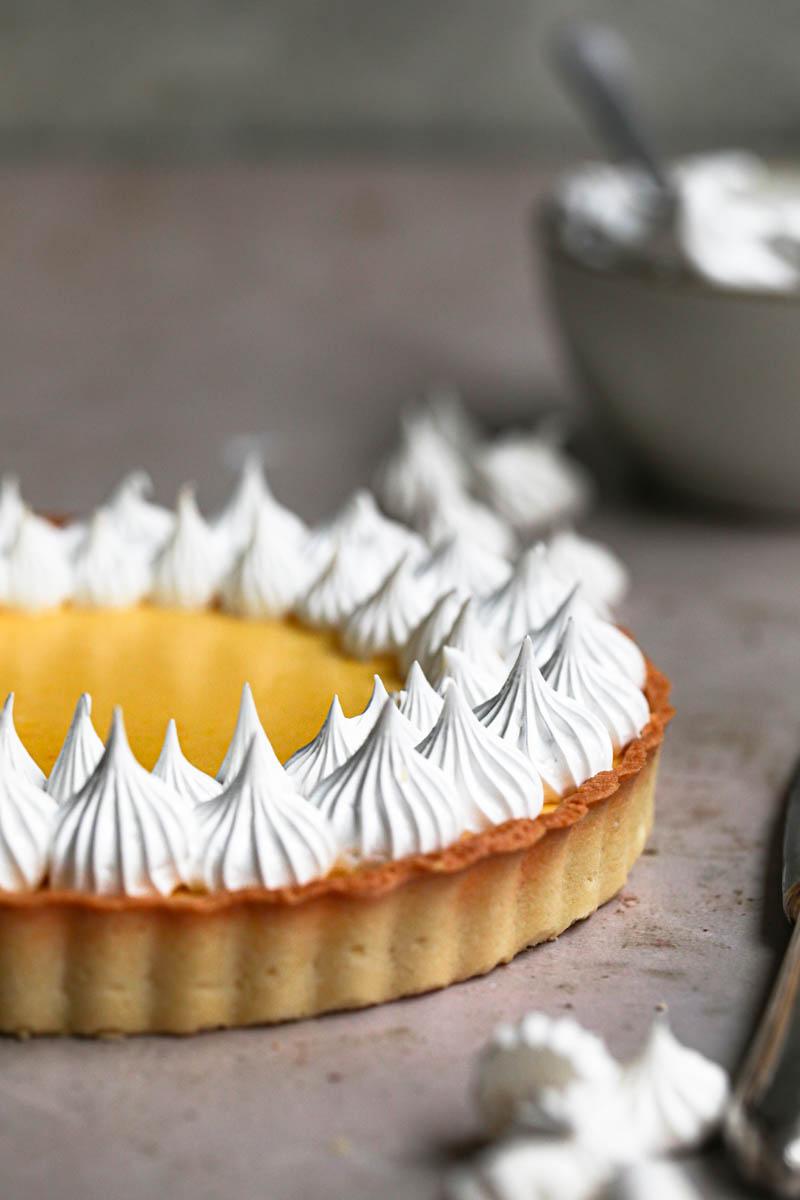 Mitad de la tarta de limón cubierta con merengue suizo con un bol pequeño y una espátula por detrás.