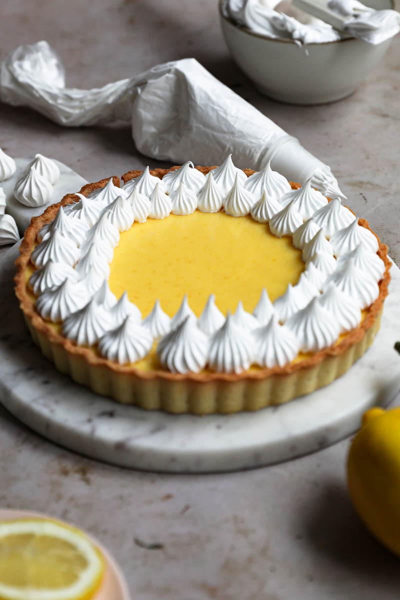 Tarta de limón con merengue sobre un plato de mármol con una manga rellena de merengue suizo detrás y algunos merenguitos danto vueltas.