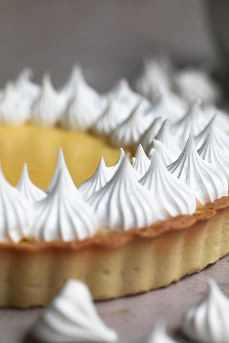 La tarta de limón cubierta con merengue con merenguitos y un bol pequeño detrás.