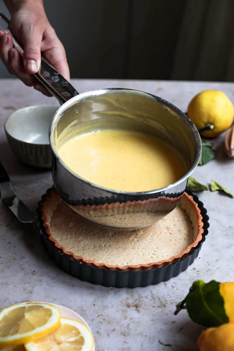 Dos manos sosteniendo el curd de limón listo dentro de la cacerola.