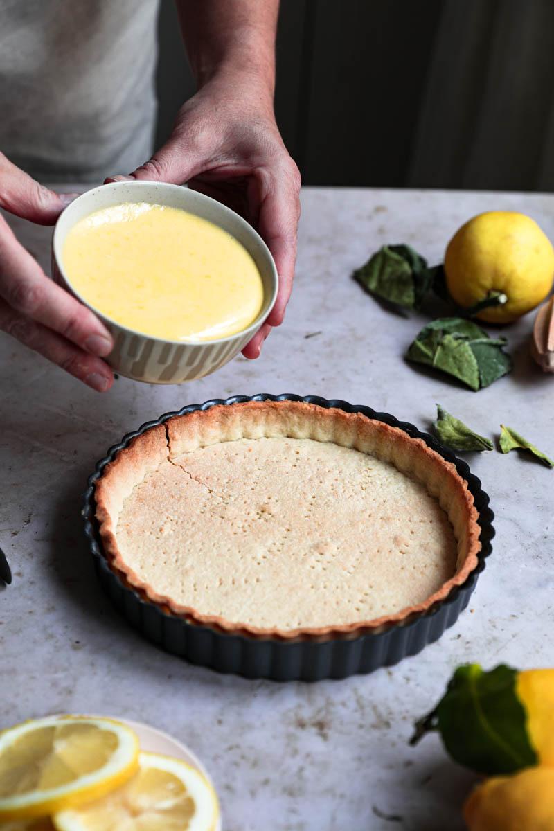 Dos manos sosteniendo un bol pequeño con el curd de limón listo para rellenar la masa de la tarta.
