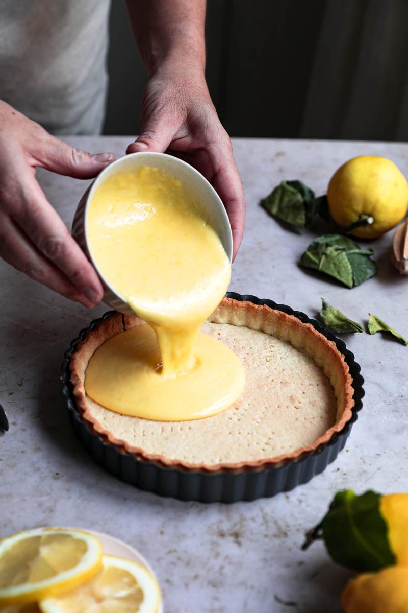 Dos manos vertiendo el curd de limón listo sobre la masa de la tarta que está rodeada de limones.
