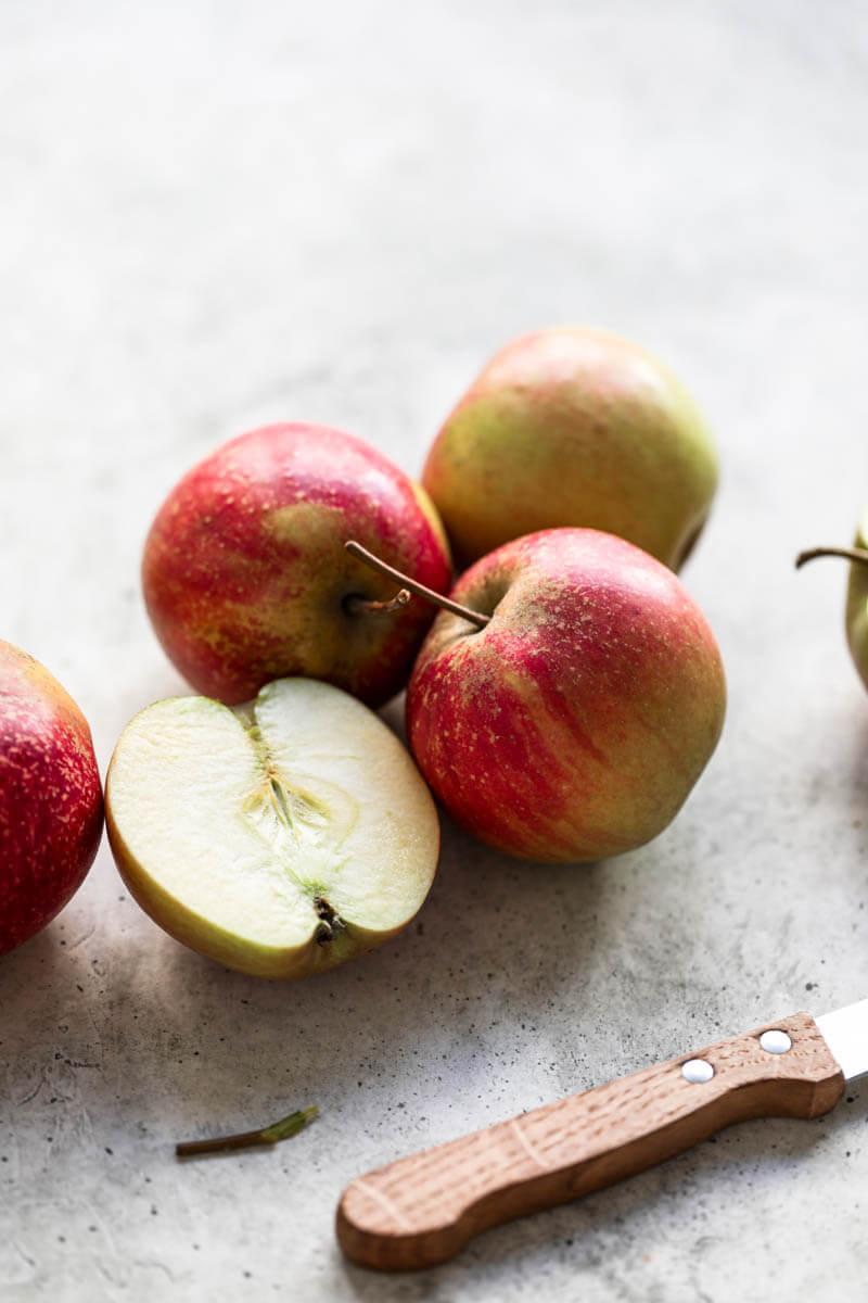 Plano de 90° de manzanas rojas con un chuchillo marron en el angulo inferior derecho