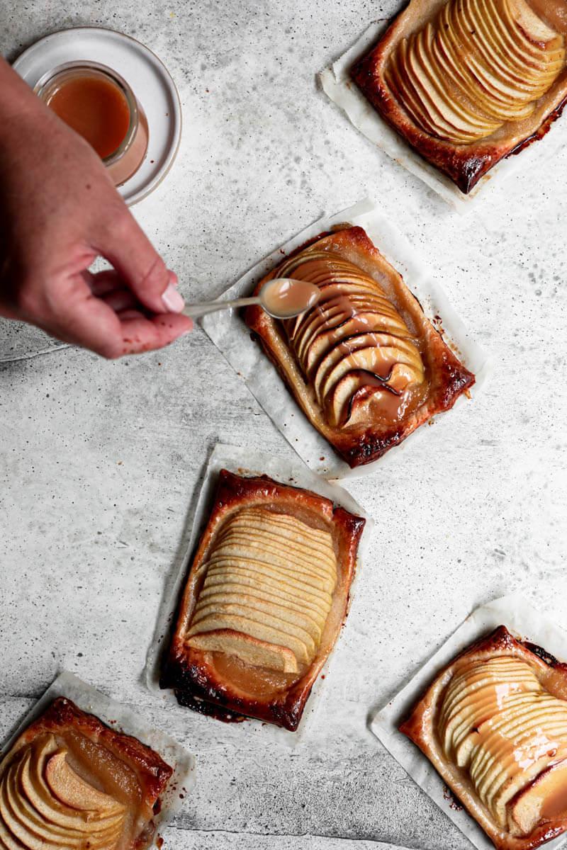 Plano aéreo de las tartas de manzana con un frasco con la salsa de caramelo en el ángulo superior izquierdo con una mano que cubre las tartas con salsa de caramelo