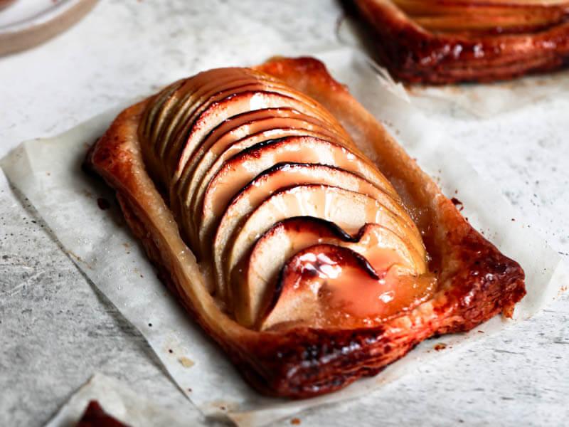 Primer plano a 45° shot de una mini tarta de manzana con masa de hojaldre con salsa de caramelo