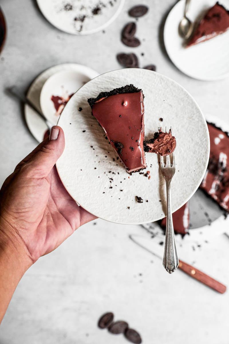 Plano aéreo de una mano sosteniendo un plato blanco con una porción de tarta de mousse de chocolate