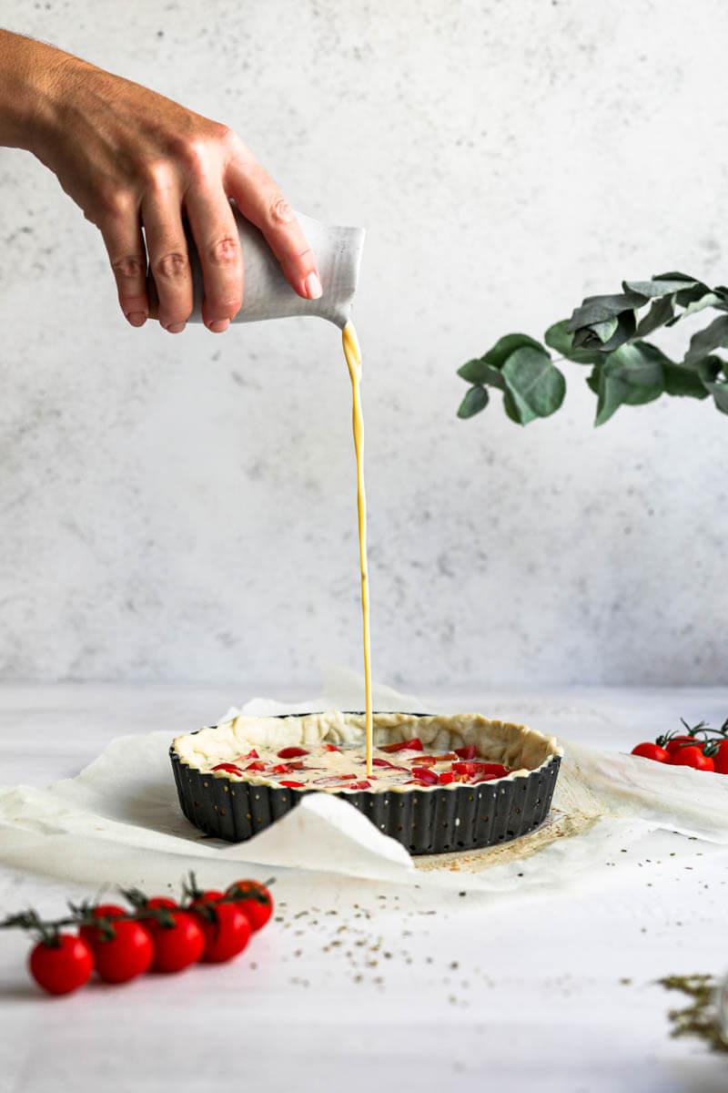 Plano de 90° de una mano rellenando la tarta con el aparto para quiche